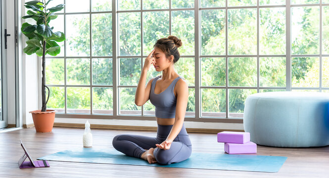 A Yoga performer meditating before start a yoga session with tablet in front