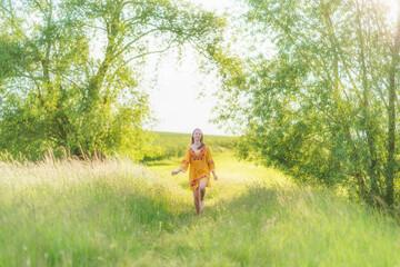 junges Mädchen posiert in der Natur im gelben Sommerkleid im lichtdurchfluteten Abendlicht.