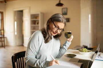 Concentrated middle aged female teacher in glasses sitting at desk drinking coffee, handwriting in...