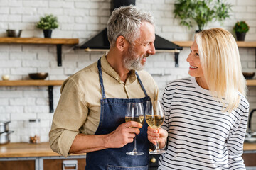 Happy senior couple drinking wine at kitchen while cooking