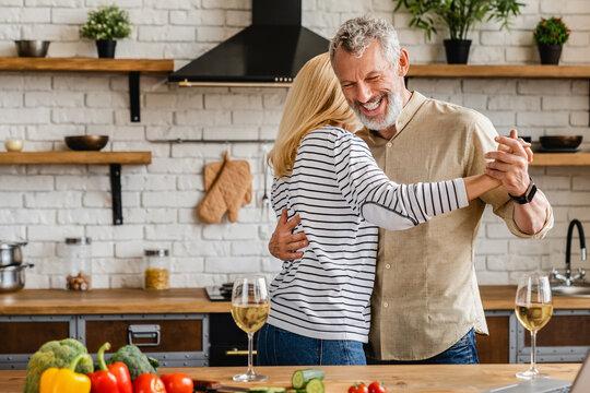 Romantic senior couple having fun while dancing at home