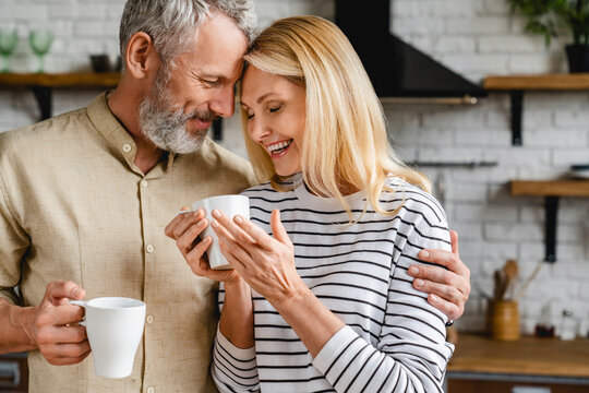 Affectionate mature couple bonding and enjoying cup of coffee