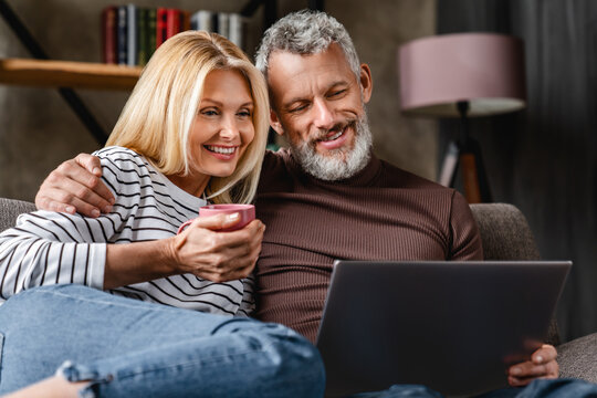 Happy beautiful middle aged couple using laptop and smiling while resting on couch at home
