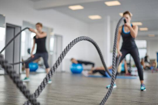 Funktionelles Training mit Seilen, Seiltrommeln (Battle Rope) in einen Fitnessstudio vor einer Spiegel Wand