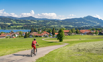 pretty senior woman riding her electrical mountain bike in warm  sunlight and enjoying the spectacular view over the Allgau alps near Moosdorf with Rottach lake and Gruenten summit, Bavaria, Germany
