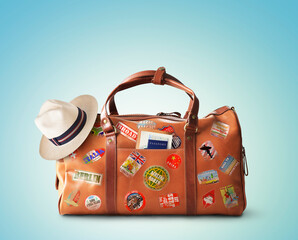 Vacation concept, large classic brown leather travel bag with hat