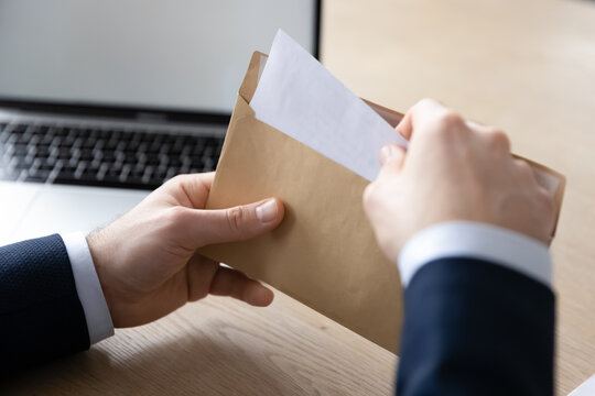 Close up back view of businessman sit at office desk open envelope with postal paper document, male employee unpack post paperwork letter or correspondence with decision notification or law order