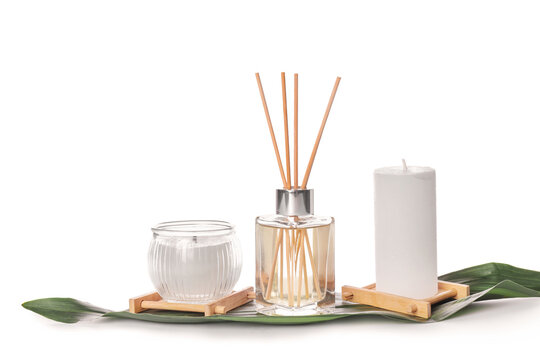 Reed diffuser and candles on white background