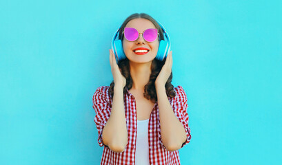 Papiers peints Magasin de musique Portrait of cheerful woman in wireless headphones listening to music wearing a pink sunglasses on colorful blue background