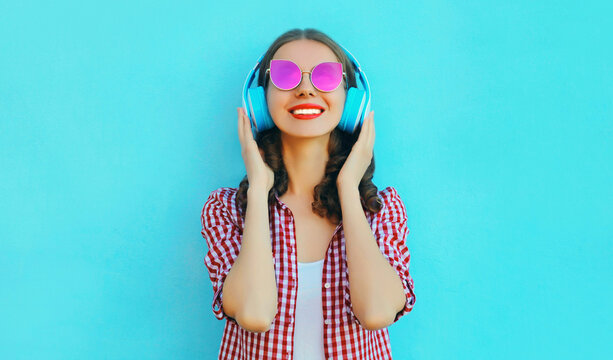 Portrait of cheerful woman in wireless headphones listening to music wearing a pink sunglasses on colorful blue background