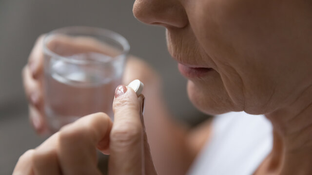 Close up of mature sick woman having antibiotic aspirin pill suffering from headache or migraine, ill senior female take daily dose of vitamin or supplement, medications, elderly healthcare concept