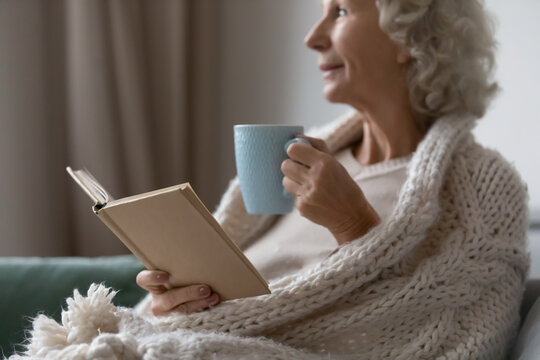 Close up of dreamy elderly woman relax on couch in living room, drink tea read book novel on weekend, happy mature grandmother look in distance thinking, enjoying cozy evening at home, hobby concept