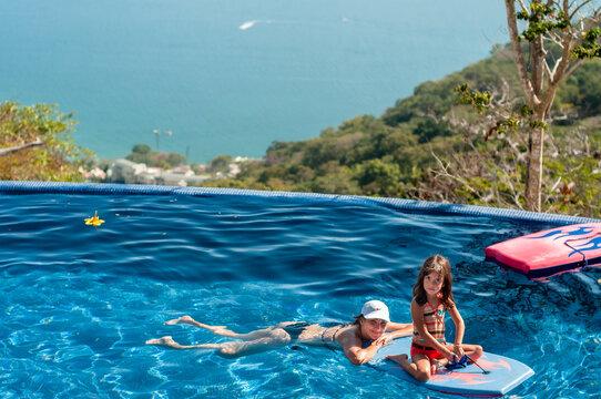 Madre y niña en alberca durante vacación de verano en Acapulco