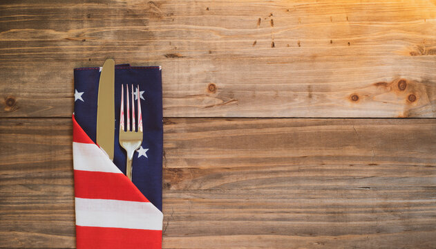 Fourth of July Table Place Setting with silverware and flag napkin on rustic wood background with room or space for copy, text, or your words.  It's an extra wide horizontal with warm light leaks.