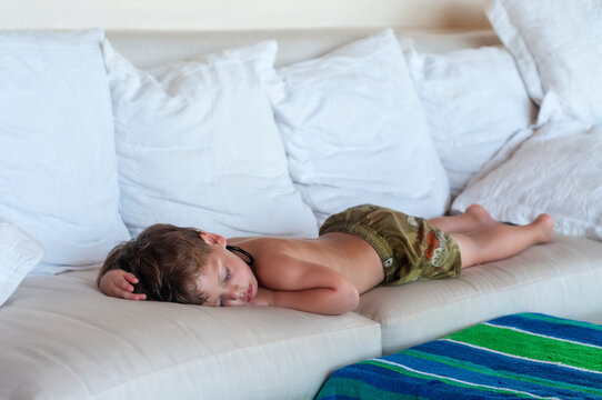 Niño duerme en sofá después de intenso día de playa en vacaciones de verano.