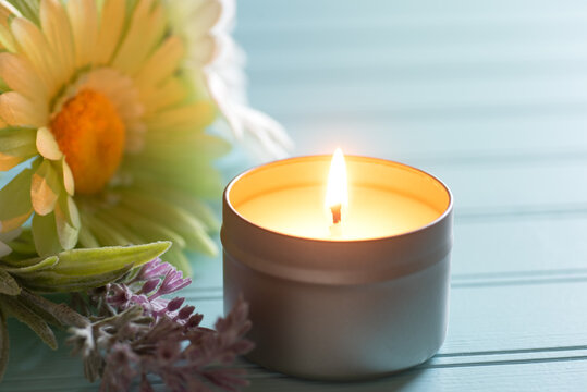 Lighted and Scented Candle in a tin holder with flowers on the side, all on teal boards table background with back window light area as copy space.  Horizontal photo with a front view