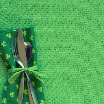 St. Patricks Day Table Placesetting with Green Shamrock Napkin and Silverware on side of burlap background with copy space.