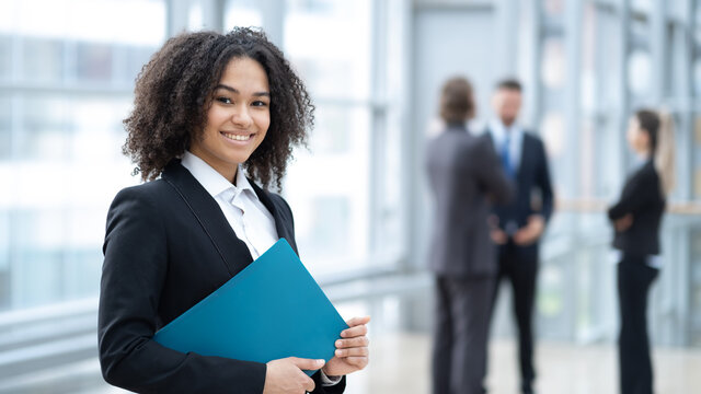 African business woman holding clipboard with colleague on background