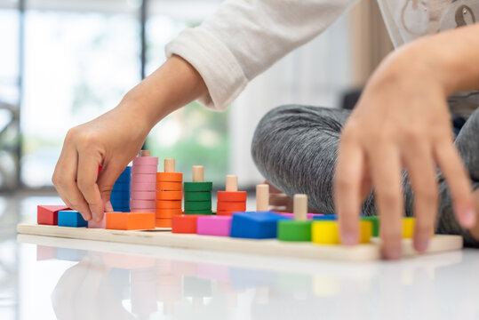 closeup of hand for girl playing color wonder blocks that a geometrical montessori puzzle of colors with constructor on floor at home, family fun at home concept