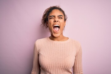 Young beautiful african american girl wearing casual sweater standing over pink background angry and mad screaming frustrated and furious, shouting with anger. Rage and aggressive concept.