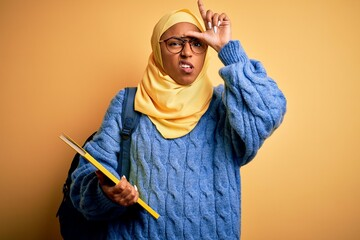 Young African American student woman wearing muslim hijab and backpack holding book making fun of people with fingers on forehead doing loser gesture mocking and insulting.