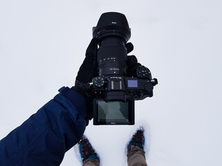 KAZA, INDIA - Dec 16, 2019: A Travel Photographer with a Nikon Mirror less Camera in the snow trying to frame his image