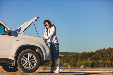 woman standing near car with opened hood on sunset talking on phone Fotobehang