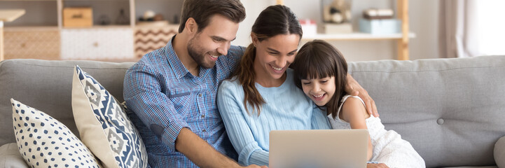 Couple and little daughter sit on sofa using pc watching cartoons on-line, surfing internet, buying...