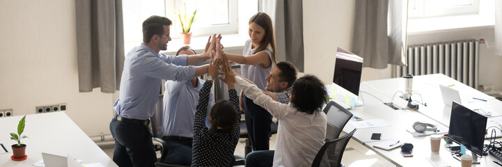 Group of multi ethnic employees gathered in co-working celebrating successful project accomplishment giving high five. Teamwork, teambuilding concept. Horizontal photo banner for website header design