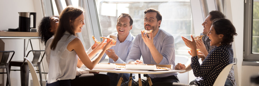 Multiethnic staff gathered together in office kitchen enjoy lunch eat pizza telling funny life stories laughing. Teambuilding corporate party concept. Horizontal photo banner for website header design