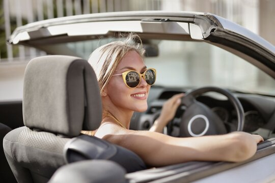 Blonde woman with sunglasses driving a car