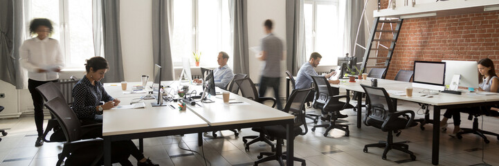 Group of multi ethnic corporate employees working in co-working open space walking in motion, sit...