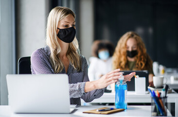Young woman with face mask back at work in office after lockdown, disinfecting hands. Wall mural