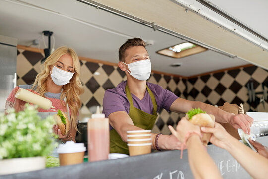 street sale and people concept - young sellers wearing face protective medical mask for protection from virus disease serving customers at food truck