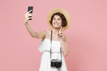 Smiling tourist girl in dress hat photo camera isolated on pink background. Traveling to travel weekends getaway. Air flight journey concept. Doing selfie shot on mobile phone, showing victory sign.