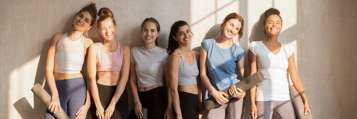 Six diverse girls wear active wear resting after work out holding mats looking at camera. Sport club trainers, happy sportive women portrait concept. Horizontal photo banner for website header design