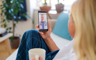 Senior woman with smartphone at home, consulting doctor and video call concept.