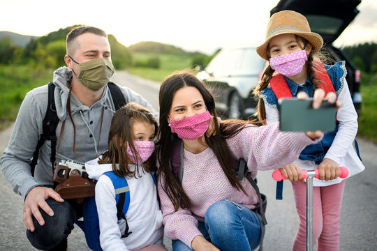 Family with two small daughters and face masks on trip outdoors in nature, taking selfie.