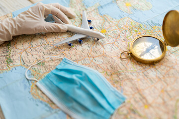 Fotobehang Noord Europa airplane taking off. travel agency working table. map, toy plane, compass, face mask and trip planning after quarantine restrictions due to epidemic covid corona virus. Tourism industry crisis bans