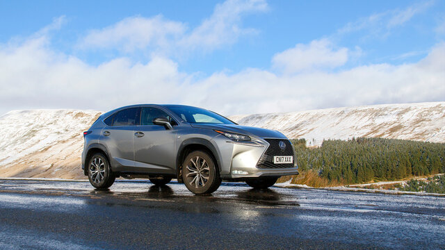 Brecon Beacons, UK: January 30, 2019: A Lexus NX 300h F-Sport crossover hybrid car on the road side in snow and dangerous icy conditions with natural light and blue sky background.