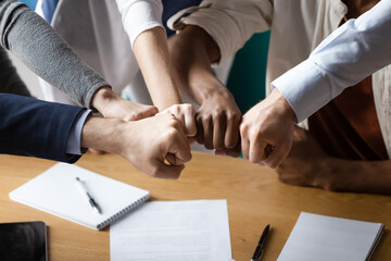 Close up image multi racial businesspeople associates putting fists together showing strong support synergy and business loyalty. Symbol of effective teamwork, trust reliability and motivation concept