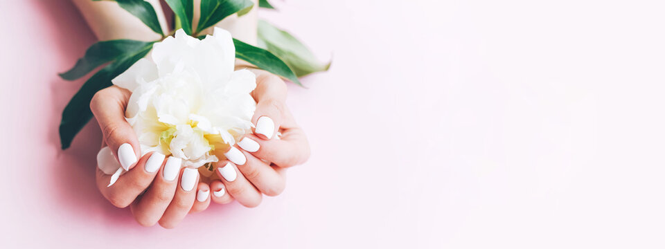 Banner for the site with a female white manicure and peony.