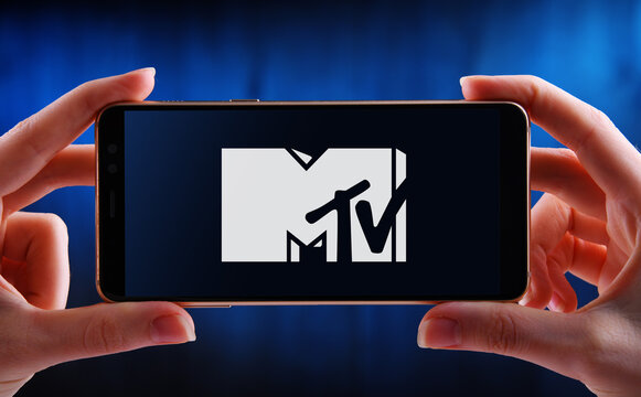 Hand holding smartphone displaying logo of MTV