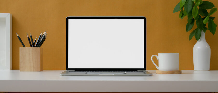 Creative worktable with mock-up laptop, stationery, cup and decorations on white table with yellow wall