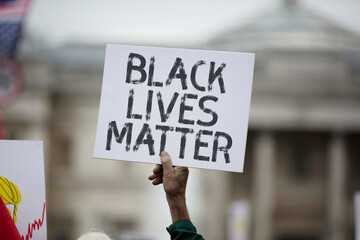 A person holding a black lives matter banner at a protest
