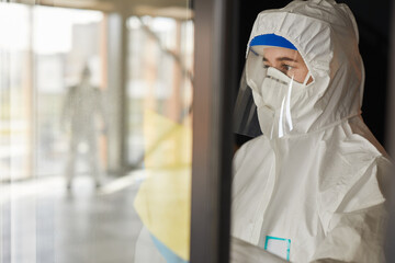 Waist up portrait of female worker wearing protective suit cleaning glass windows indoors during disinfection, copy space