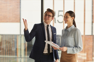 Waist up portrait of smiling real estate agent discussing property with female client and pointing up while standing in empty office building interior lit by sunlight, copy space
