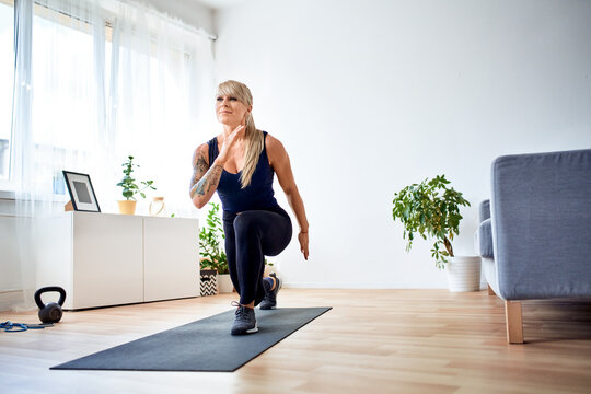 Happy athletic woman doing home workout practicing lunges exercise