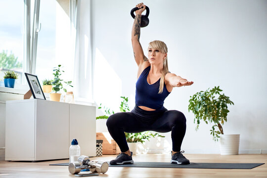 Athletic woman doing squats with kettlebell during home workout