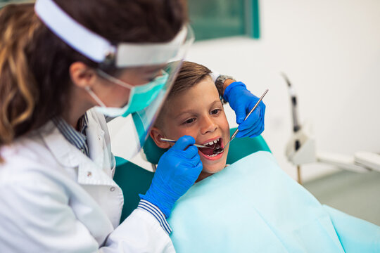 Cute little boy sitting on dental chair and having dental treatment.